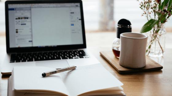 PirraSmith - portatil abierto y cuaderno con boli y taza de te dispuesto para escribir