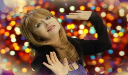 Comedian Judy Tenuta with sparkling lights behind her