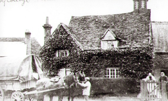 1890s Charles and Phoebe Burton, standing at the gates of Ivy Cottage, opposite the church. The Burtons were smallholders and also bought and sold animal food. The miller's wagon, covered with the canvas tilt, could be delivering or collecting from the extensive barns to the right of the cottage.