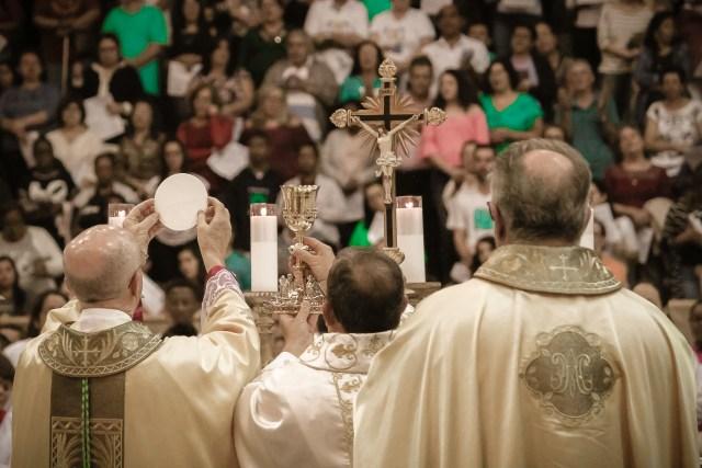 Padres celebrando missa no fundo assembleia