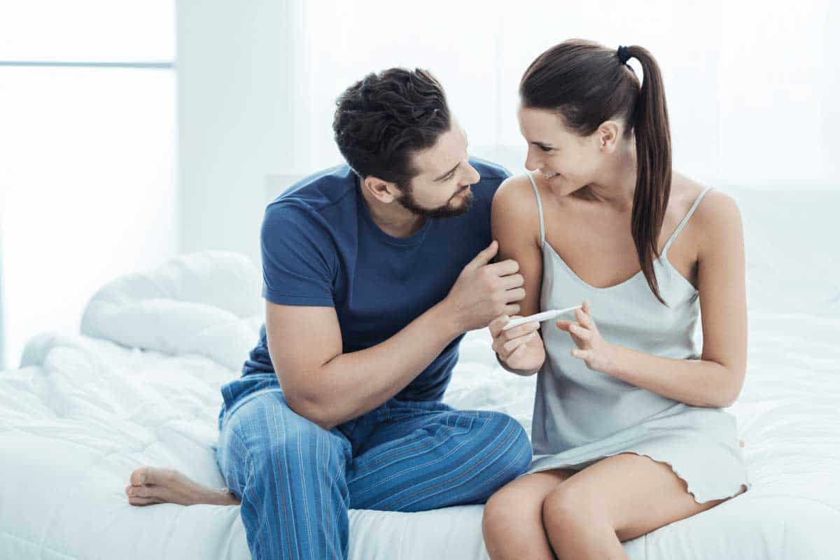 A man and a women sitting on a bed smiling, looking at each other with a positive pregnancy test between them because they increased their chances of getting pregnant naturally