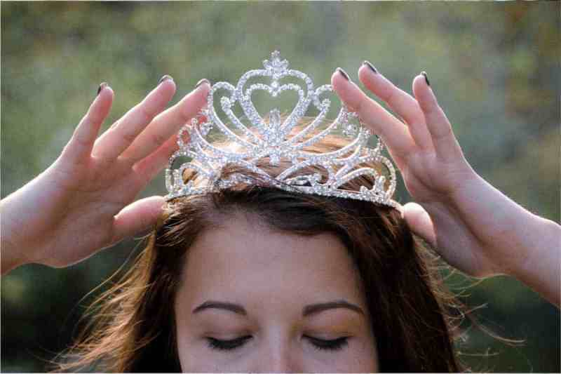 A woman putting a crown on her head because she has discovered ovulation tests as a natural way to get pregnant