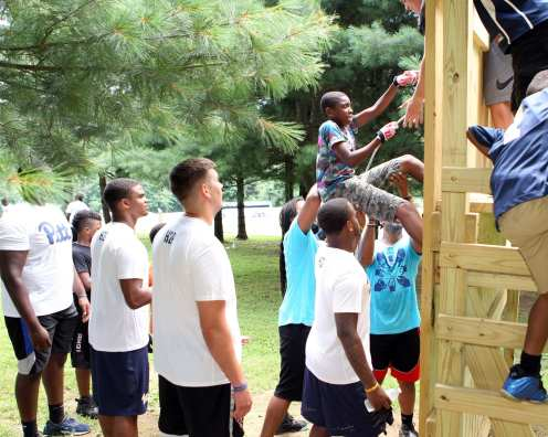 Pitt Freshman help a kid climb a wall at the Mel Blount Youth Leadership Initiative (Photo by David Hague)