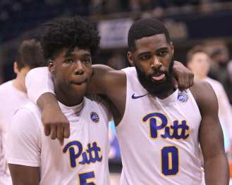 Jared Wilson-Frame (0) and Marcus Carr (5) walk off arm in arm after getting beat by Syracuse on January 27, 2018 -- DAVID HAGUE