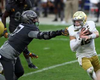 Ian Book (12) of Notre Dame evades Rashad Weaver (17) October 24, 2020 David Hague/PSN