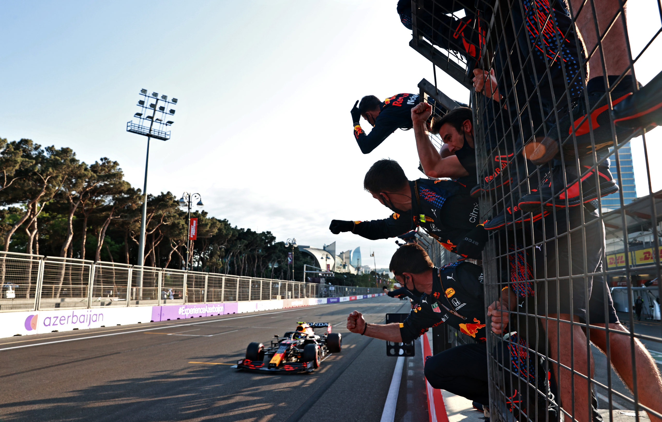 BAKU, AZERBAIJAN - JUNE 06: Sergio Perez of Mexico driving the (11) Red Bull Racing RB16B Honda crosses the finish line to win as Red Bull Racing team members celebrate on the pitwall during the F1 Grand Prix of Azerbaijan at Baku City Circuit on June 06, 2021 in Baku, Azerbaijan. (Photo by Mark Thompson/Getty Images) // Getty Images / Red Bull Content Pool  // SI202106060294 // Usage for editorial use only //