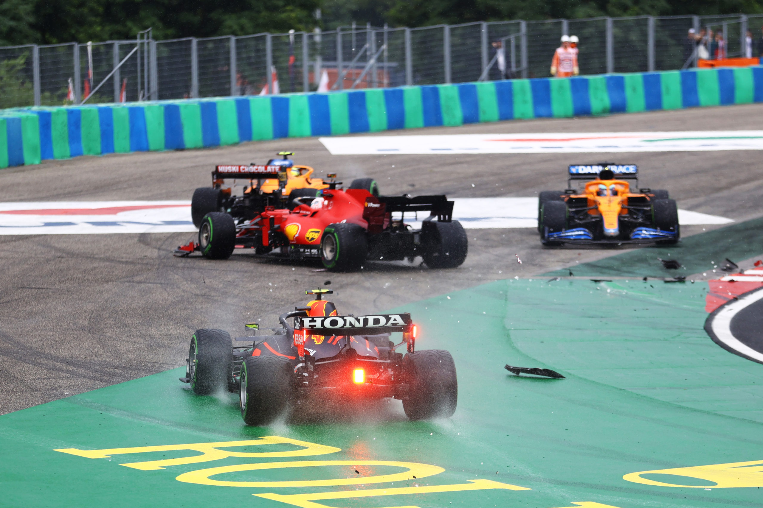 BUDAPEST, HUNGARY - AUGUST 01: Sergio Perez of Mexico driving the (11) Red Bull Racing RB16B Honda runs wide at the start as cars tangle ahead of him during the F1 Grand Prix of Hungary at Hungaroring on August 01, 2021 in Budapest, Hungary. (Photo by Bryn Lennon/Getty Images) // Getty Images / Red Bull Content Pool  // SI202108010225 // Usage for editorial use only //
