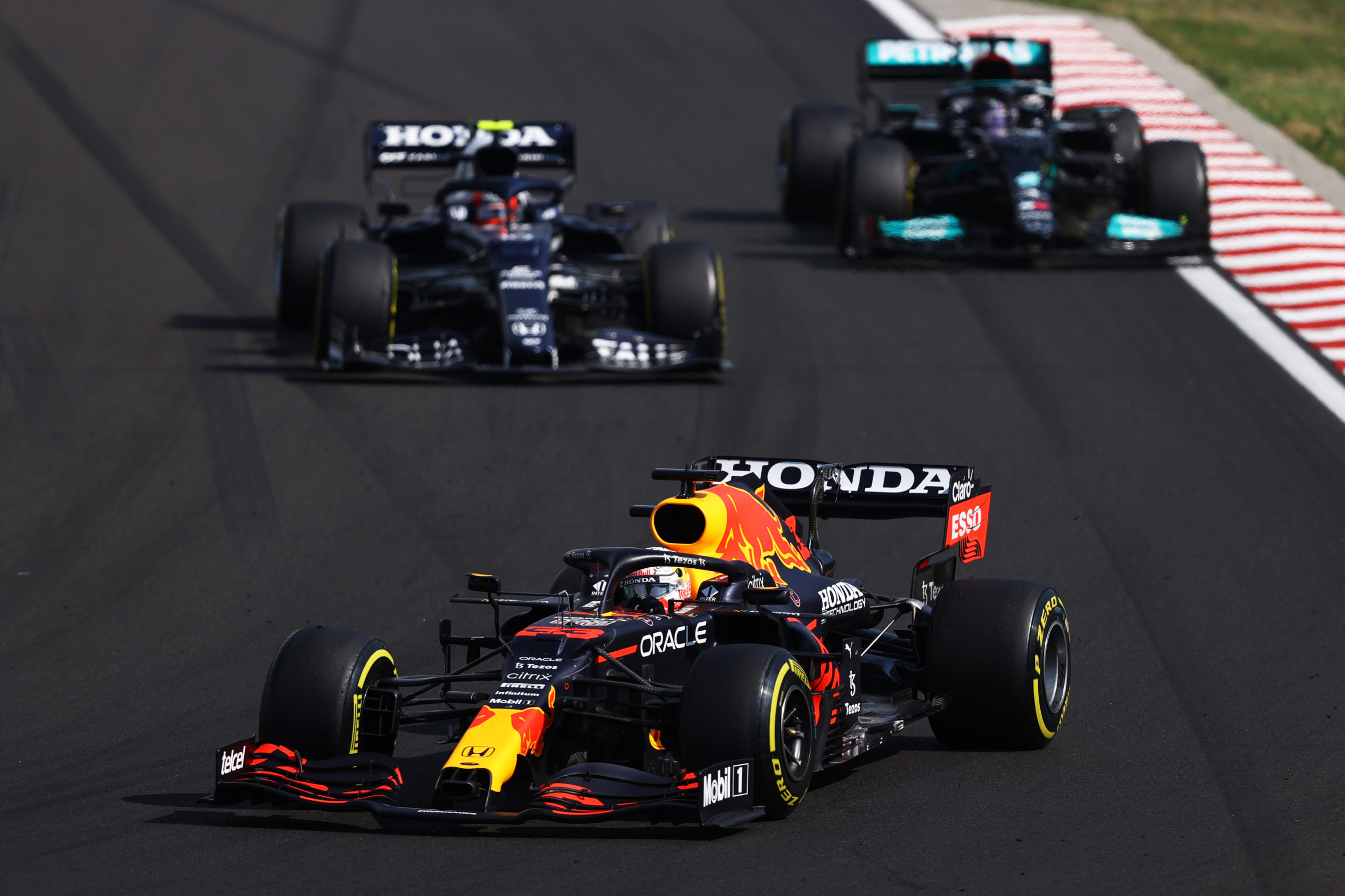 BUDAPEST, HUNGARY - AUGUST 01: Max Verstappen of the Netherlands driving the (33) Red Bull Racing RB16B Honda leads Pierre Gasly of France driving the (10) Scuderia AlphaTauri AT02 Honda and Lewis Hamilton of Great Britain driving the (44) Mercedes AMG Petronas F1 Team Mercedes W12 during the F1 Grand Prix of Hungary at Hungaroring on August 01, 2021 in Budapest, Hungary. (Photo by Bryn Lennon/Getty Images) // Getty Images / Red Bull Content Pool  // SI202108010277 // Usage for editorial use only //
