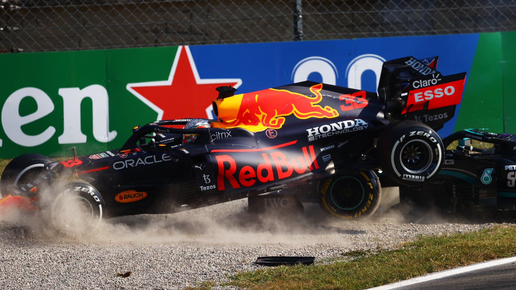 MONZA, ITALY - SEPTEMBER 12: Max Verstappen of the Netherlands driving the (33) Red Bull Racing RB16B Honda and Lewis Hamilton of Great Britain driving the (44) Mercedes AMG Petronas F1 Team Mercedes W12 crash during the F1 Grand Prix of Italy at Autodromo di Monza on September 12, 2021 in Monza, Italy. (Photo by Dan Istitene - Formula 1/Formula 1 via Getty Images)