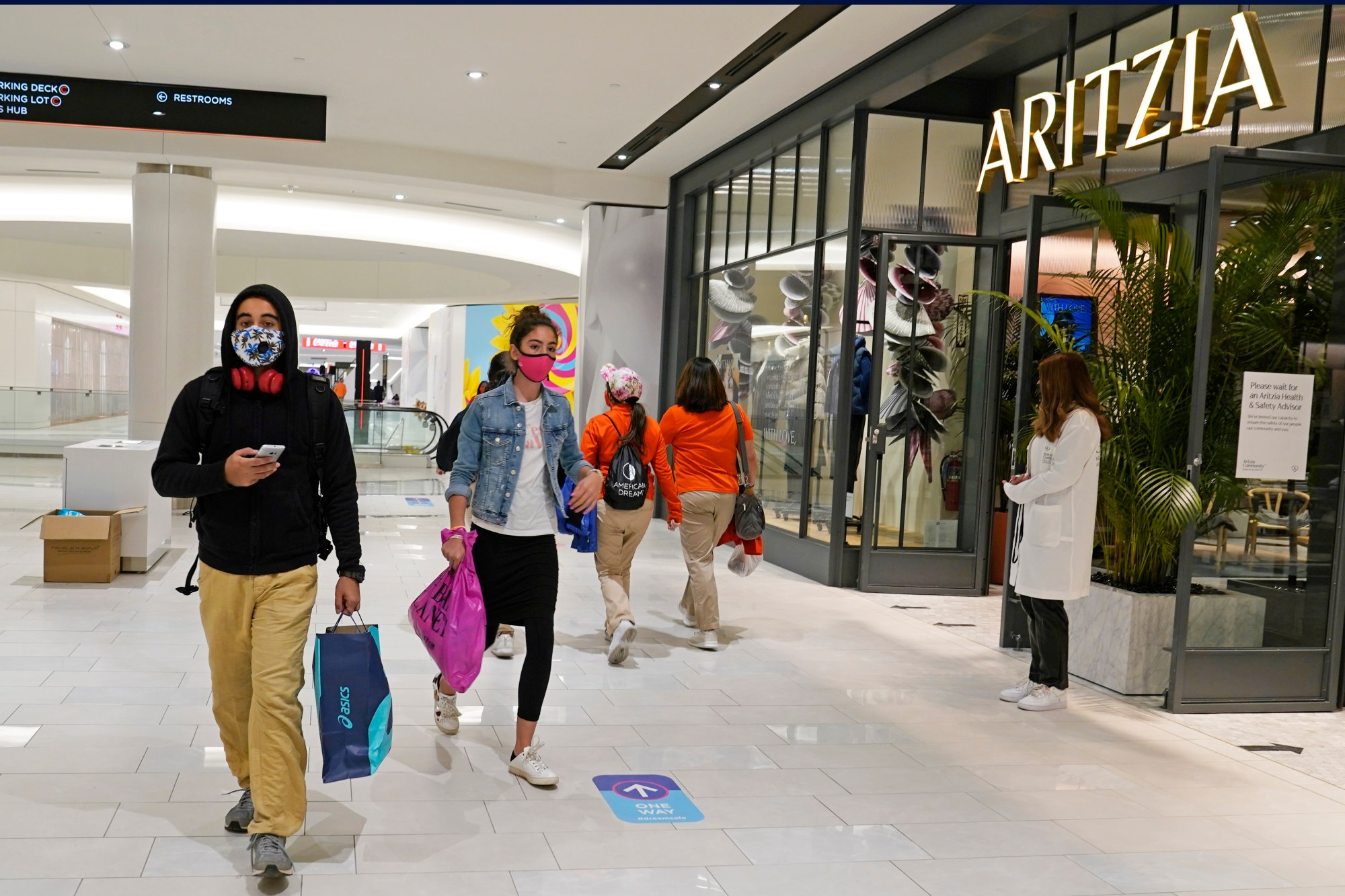 people wearing masks to protect against covid walk in New Jersey mall