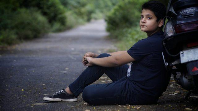 A boy sitting beside road