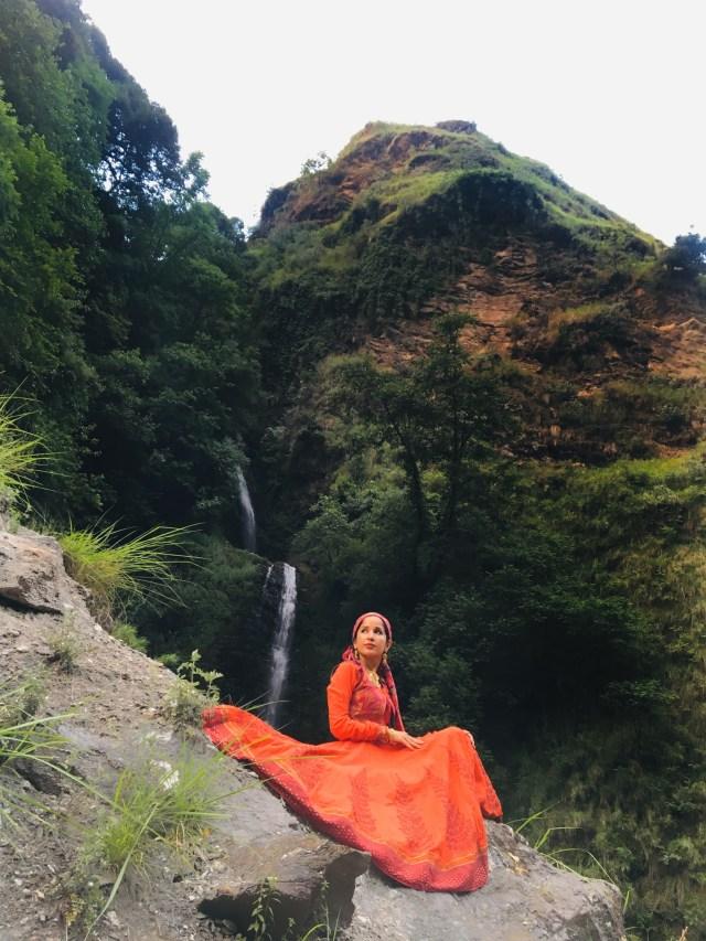 a beautiful woman sitting on a mountain
