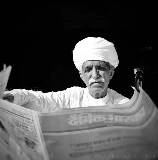old man reading news paper