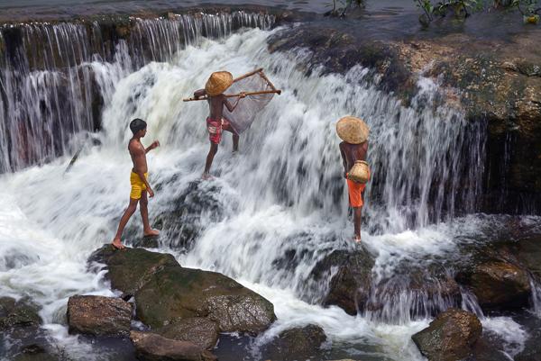 boys enjoying fishing in the waterfall
