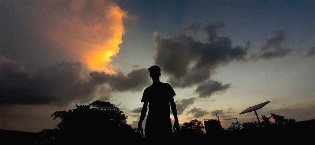 A boy enjoying sunset clouds