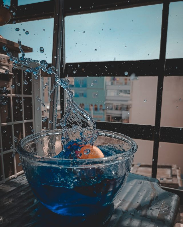 ball dropping in a bowl of blue colored water