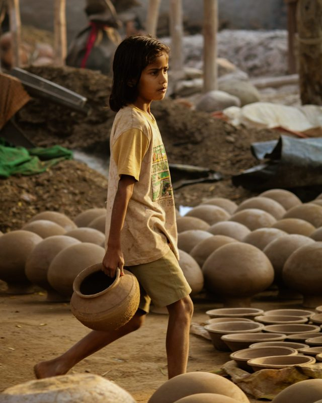 girl carrying clay pots