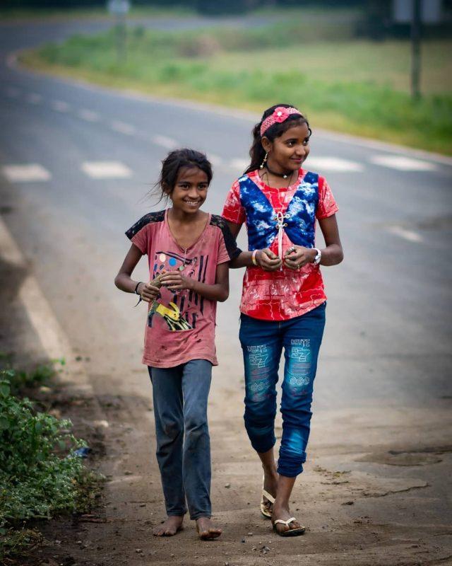 Little girls walking on a road