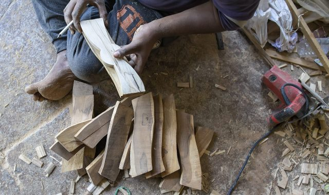 A carpenter working on wooden pieces