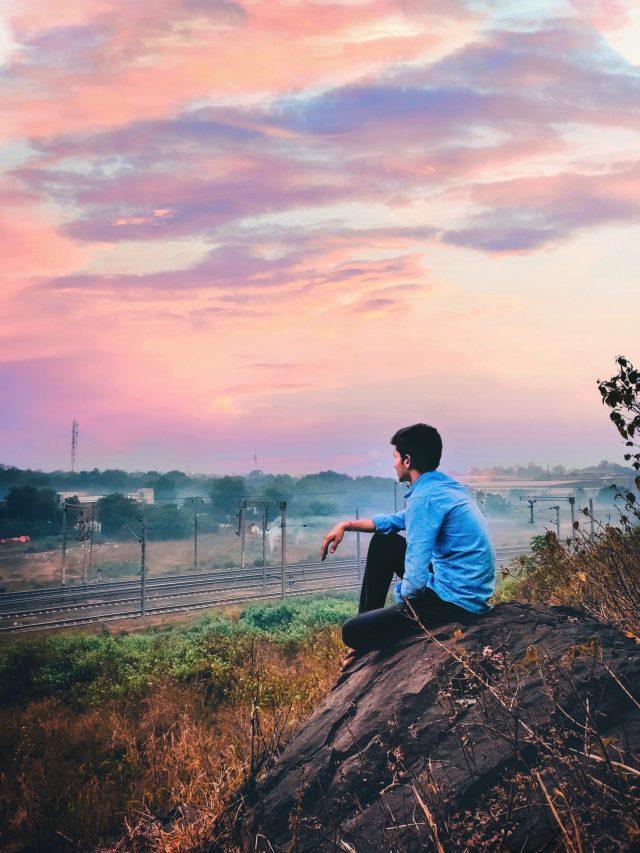 boy sitting on a rock admiring nature