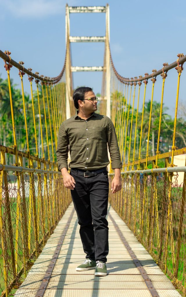 A person posing on a hanging bridge