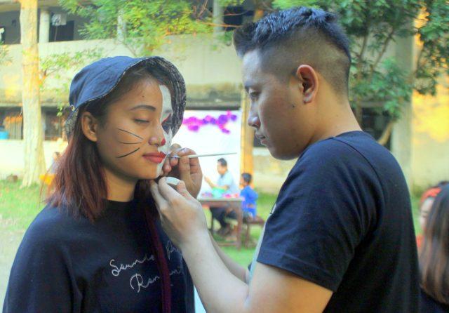 Artist doing face painting on girl's face