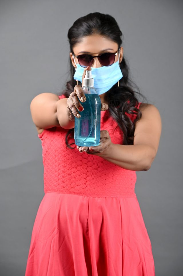 Girl wearing goggle and holding sanitizer