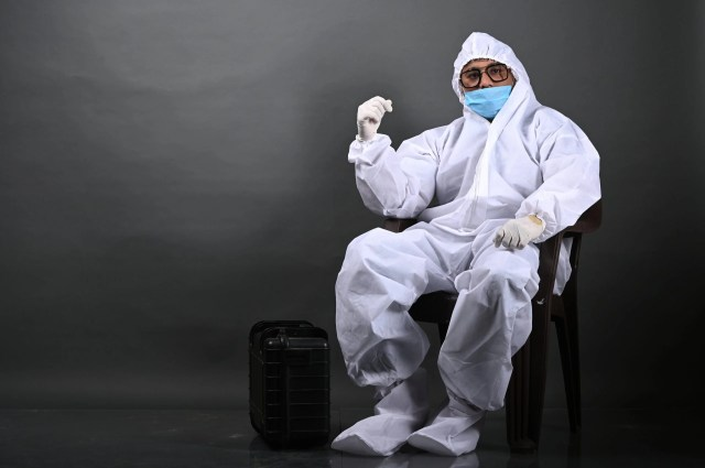Man sitting on chair in PPE kit
