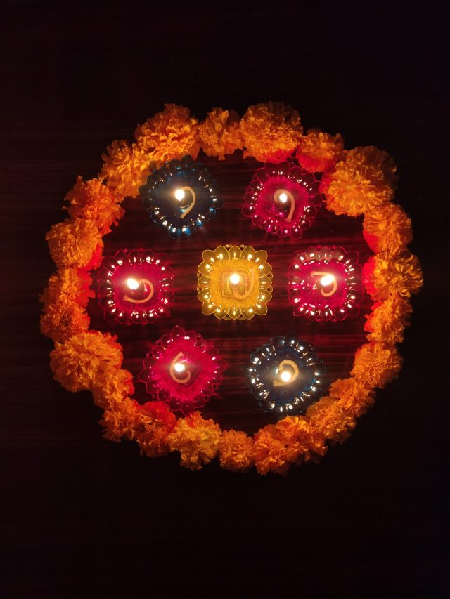A design make with flowers and oil lamps