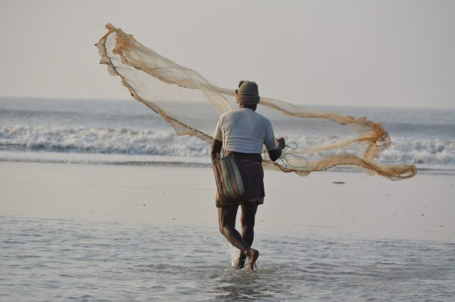 A fisherman spreading his net in water