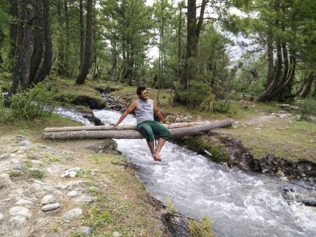 Boy sitting on wood block over a river