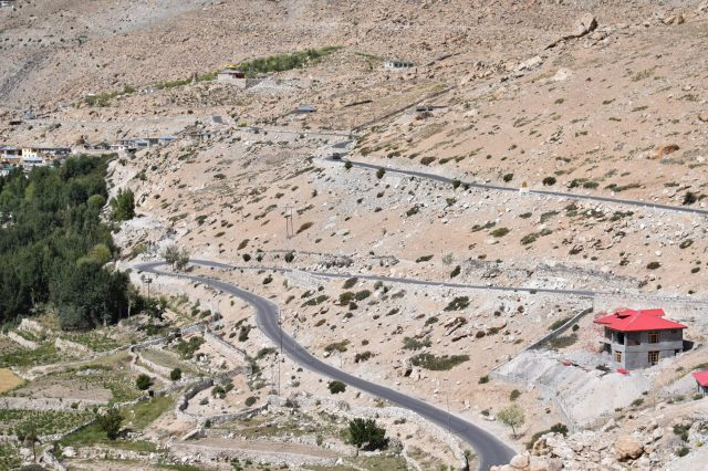 A road curves on a barren mountain