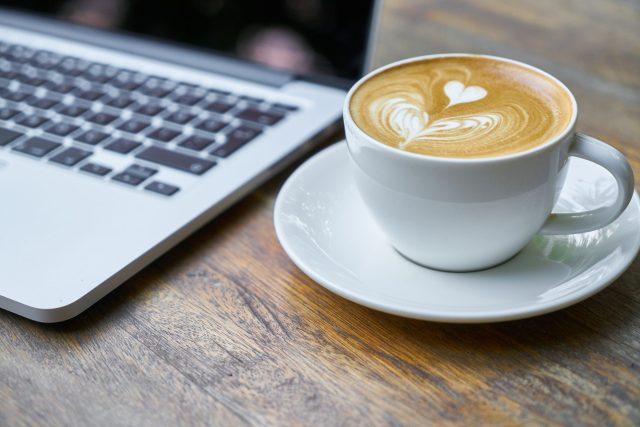 Coffee near the laptop on desk