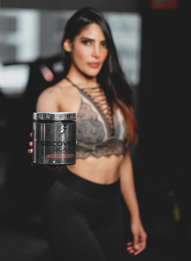 Female fitness model presenting Supplement box