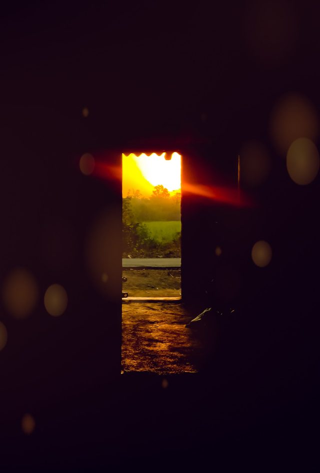 Sunrays falling in a room through a door