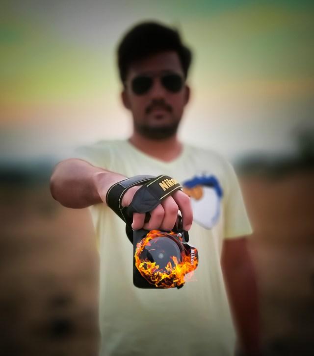A man showing a burning camera