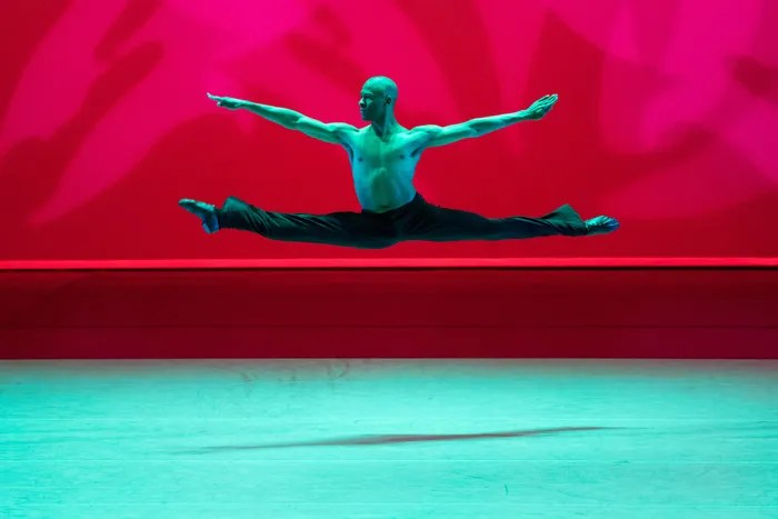 A male black dancer jumping, legs in a split, arms spread, on a ballet stage with red and blue lighting.