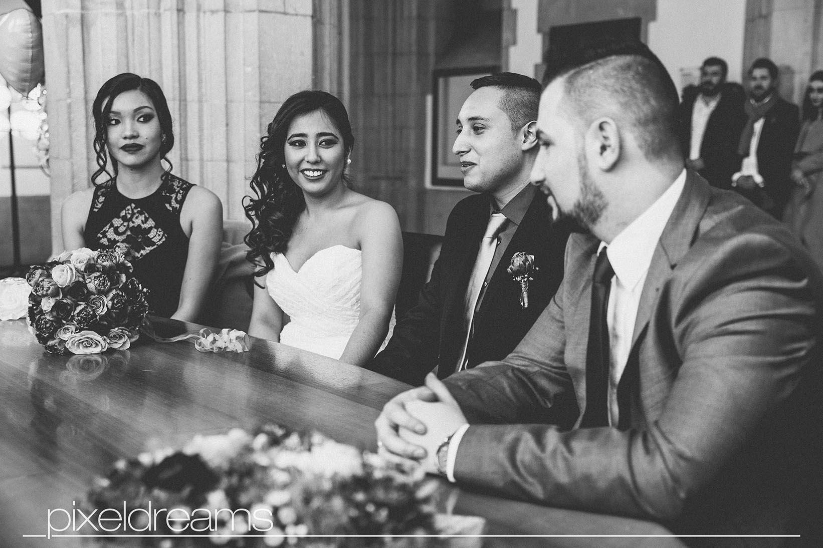 Braut und Bräutigam sitzen mit ihren Trauzeugen vor dem Standesbeamten in der Rentkammer im historischen Rathaus.