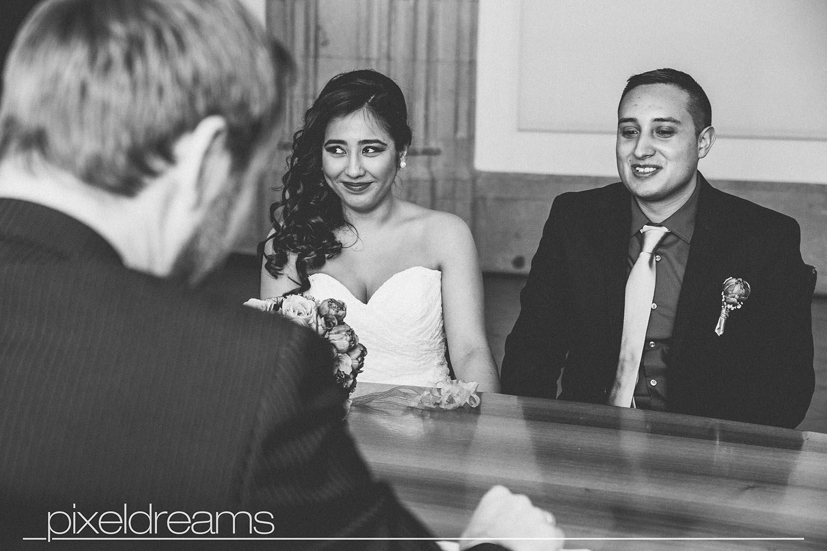 Braut und Bräutigam sitzen vor dem Standesbeamten und lassen sich gleich trauen - die reportage erfolgt durch unseren hochzeitsfotografie pixeldreams