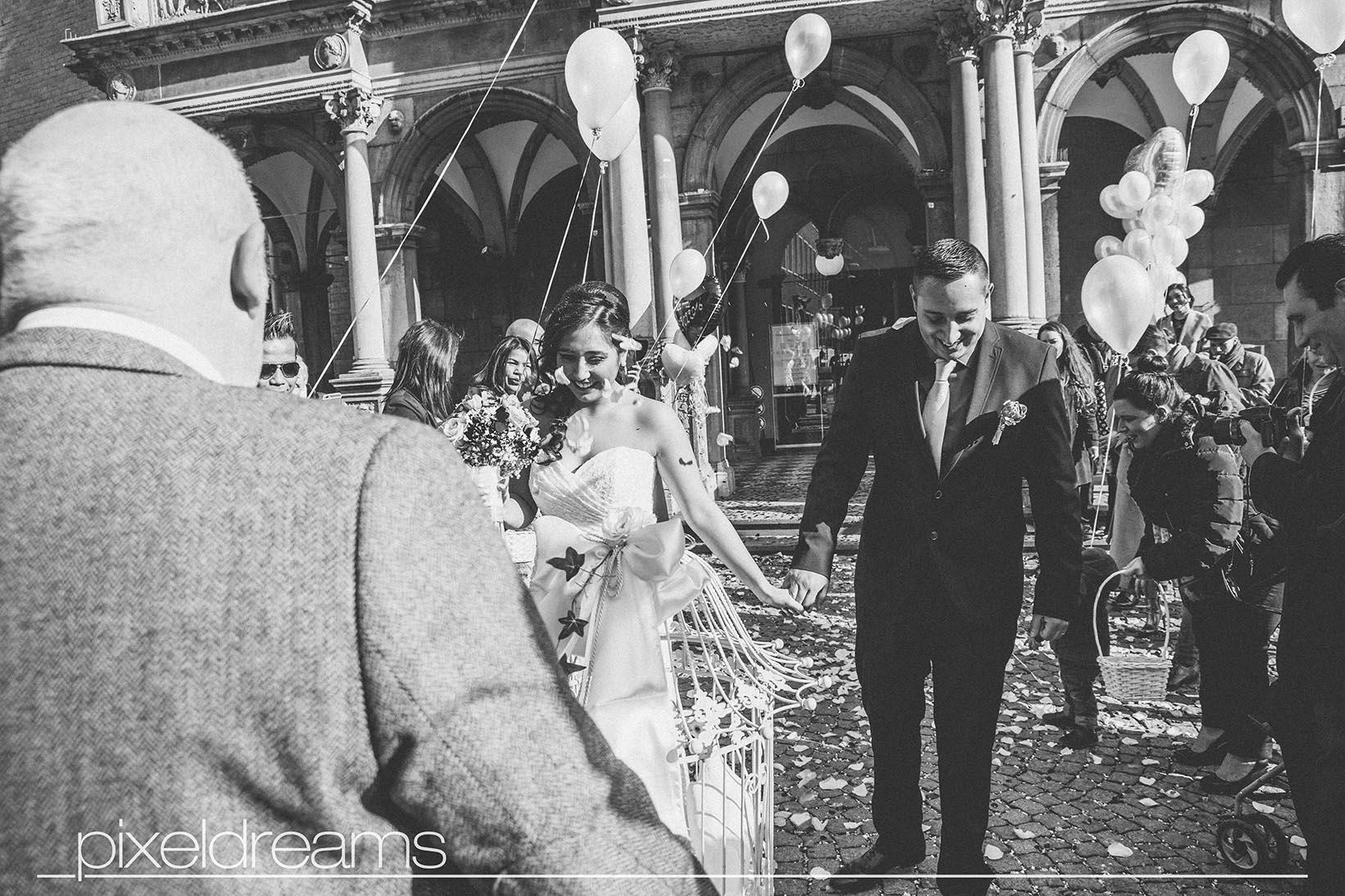 Braut und Bräutigam werden von Gästen empfangen. Sie werden gleich die weiße Hochzeitstauben zum fliegen bringen.