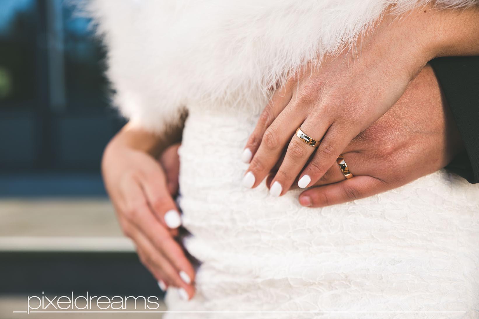 Detailaufnahme von den Trauringen / Eheringenund dem Brautkleid