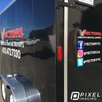 Company logo decals, vinyl lettering, and social media decals on a black work tool trailer.