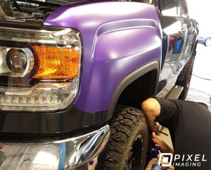 A man installing pearlescent-purple vinyl vehicle color-change wrap on a GMC 3500 HD pickup truck.