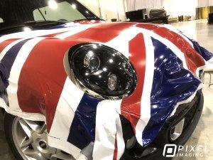 Unfinished installation of a custom-printed vinyl vehicle wrap of the United Kingdom Union Jack flag on a Cooper Mini car.