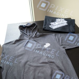 Custom hoodies Calgary: A pair of custom-printed hoodies displayed on a table featuring the logo of a Calgary business.