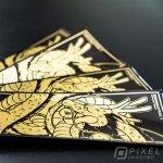 Custom Stickers Calgary: Custom-printed stickers on metallic gold showing Japanese dragon artwork.