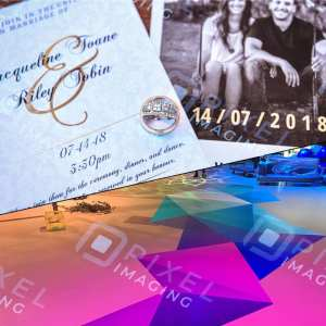 A split view of wedding invitations/wedding save the date cards with an engagement ring in the foreground, and a custom-printed vinyl floor wrap graphic at an event.