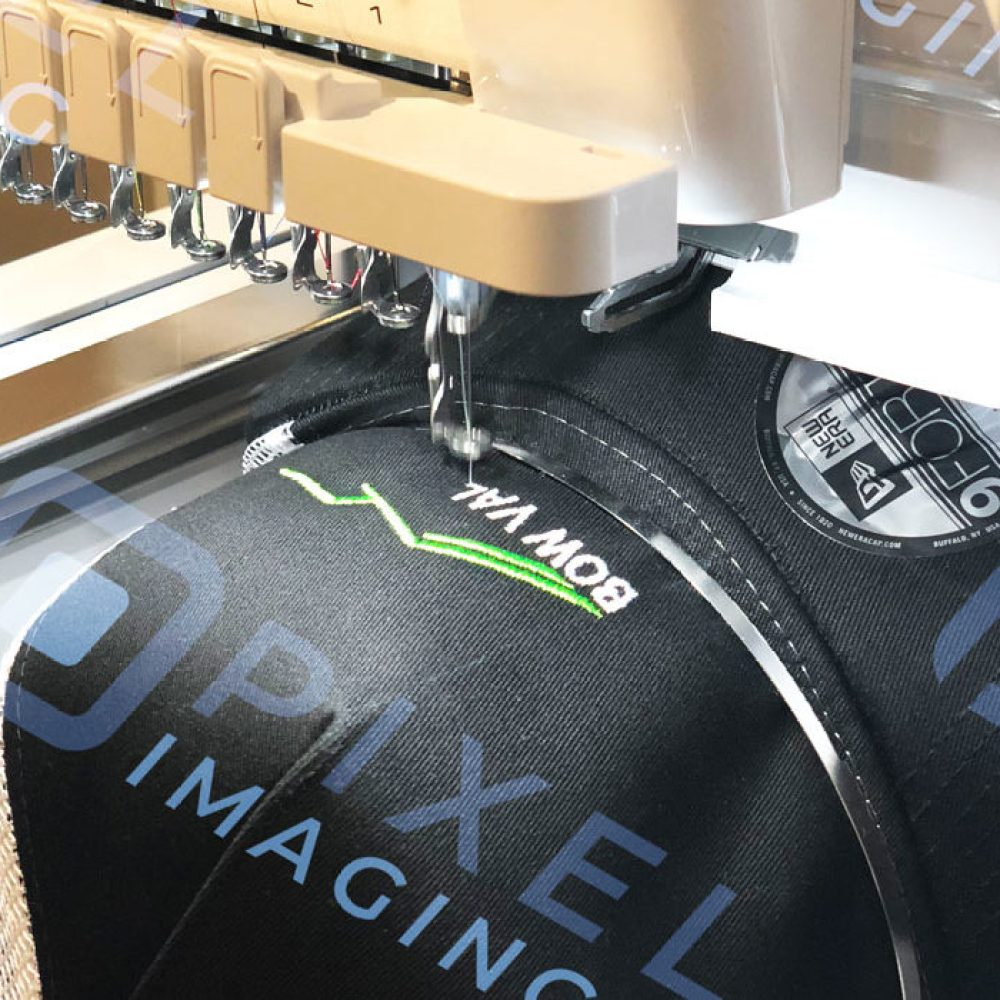 Custom-embroidered baseball cap hat being embroidered on an embroidery machine.