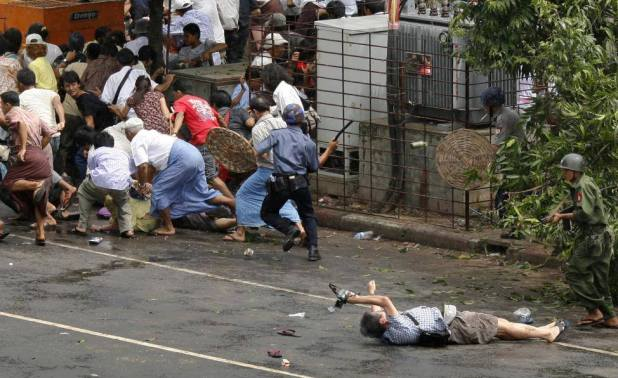 Kenji Nagai of APF tries to take photographs as he lies injured after police and military officials fired upon and then charged at protesters in Yangon's city centre September 27, 2007. Nagai, 50, a Japanese video journalist, was shot by soldiers as they fired to disperse the crowd. Nagai later died. REUTERS/Adrees Latif
