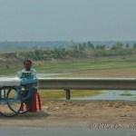 Fruit vendor on highway with Ganges in background